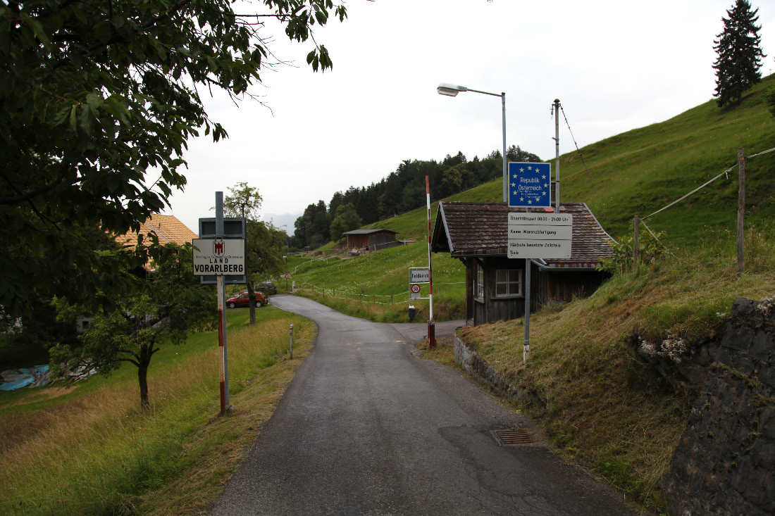 On St. Georg-Straße in the Schällabärg – Schellenberg Gemeinde of northeast Liechtenstein and looking at open road, as should be the case within European Christendom, a very few meters ahead to Fresch in Austria – Österreich