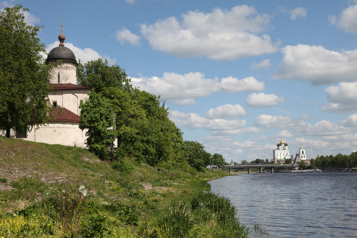 Church of Pope Saint Clement in Pskov with Krom and Trinity Cathedral in distance on opposite bank of the river