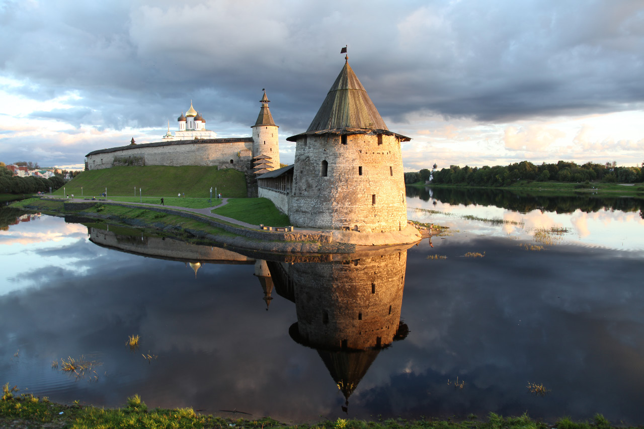 Looking toward the Pskov Kremlin and at the point where the Pskov River flows into the Great River, the Flat Tower stands nearest and is reflected in the Pskov